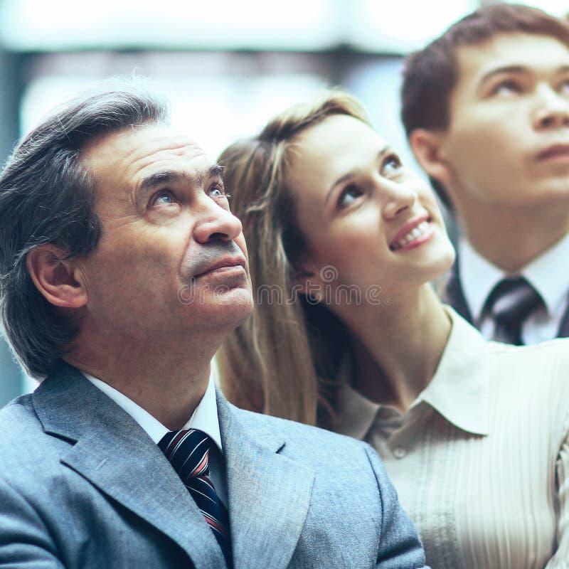 Position de sourire heureuse d'équipe d'affaires dans une rangée dans le bureau et image libre de droits
