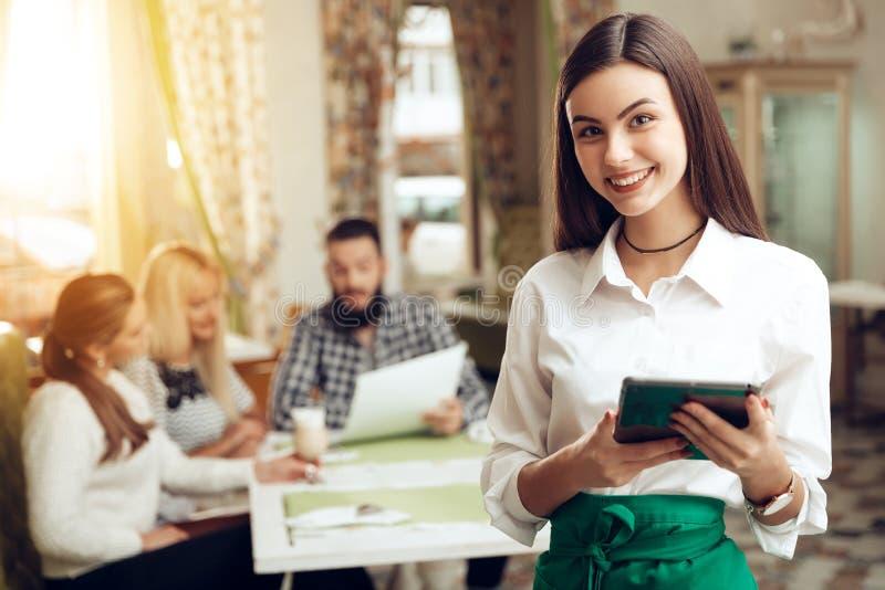 Position de sourire de serveuse de portrait jeune en café photos stock