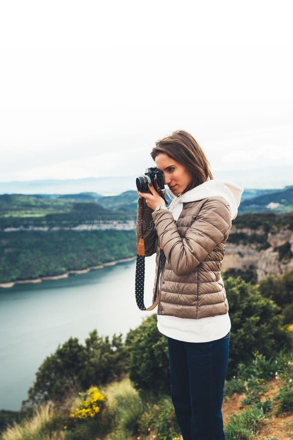 Position de touristes de voyageur de photographe sur le dessus vert sur la montagne se tenant dans la caméra numérique de photo d image libre de droits