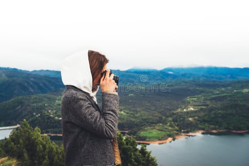 Position de touristes de voyageur de photographe sur le dessus vert sur la montagne se tenant dans la caméra numérique de photo d images stock