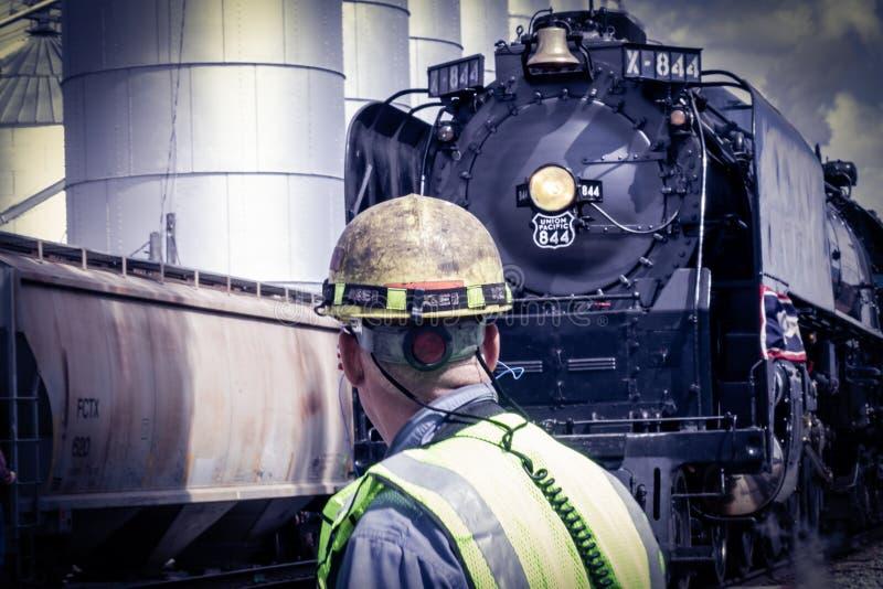 Position de travailleur de chemin de fer devant la locomotive à vapeur photo stock