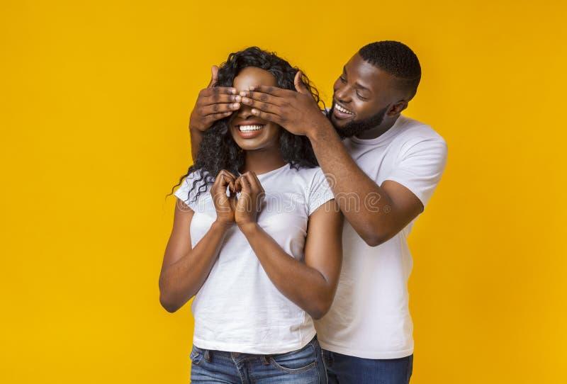 Position de type noir derrière son amie et fermeture de ses yeux images stock