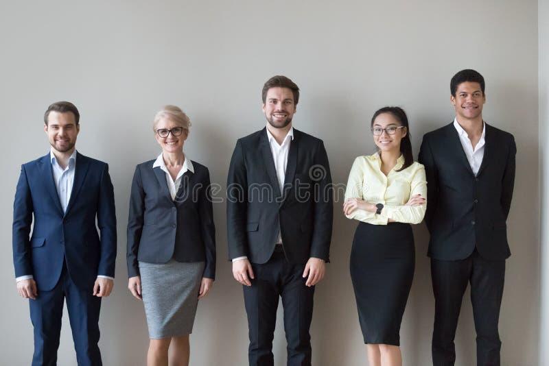 Position diverse heureuse d'équipe de cadres près de portrait de headshot de mur photographie stock