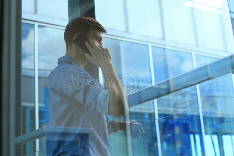 Position et à l'aide de sourire d'homme d'affaires du téléphone portable dans le bureau images libres de droits