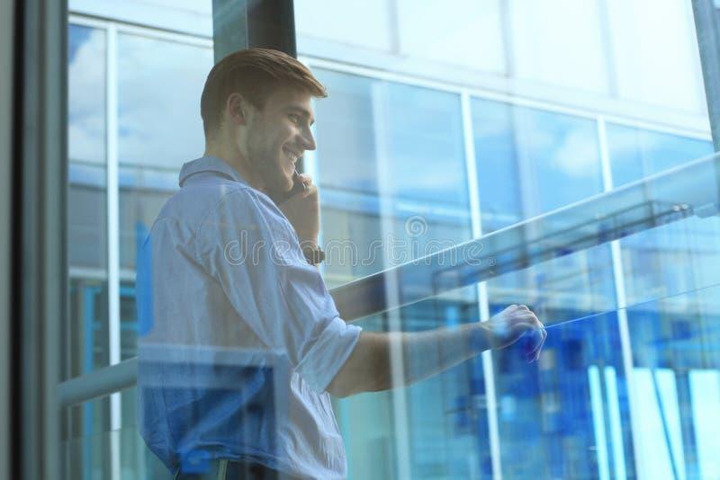 Position et à l'aide de sourire d'homme d'affaires du téléphone portable dans le bureau photo libre de droits