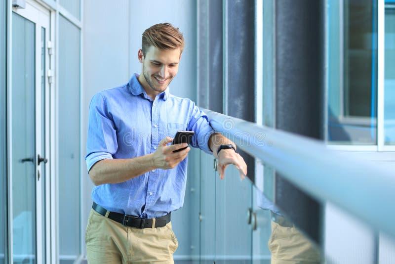 Position et à l'aide de sourire d'homme d'affaires du téléphone portable dans le bureau photos stock