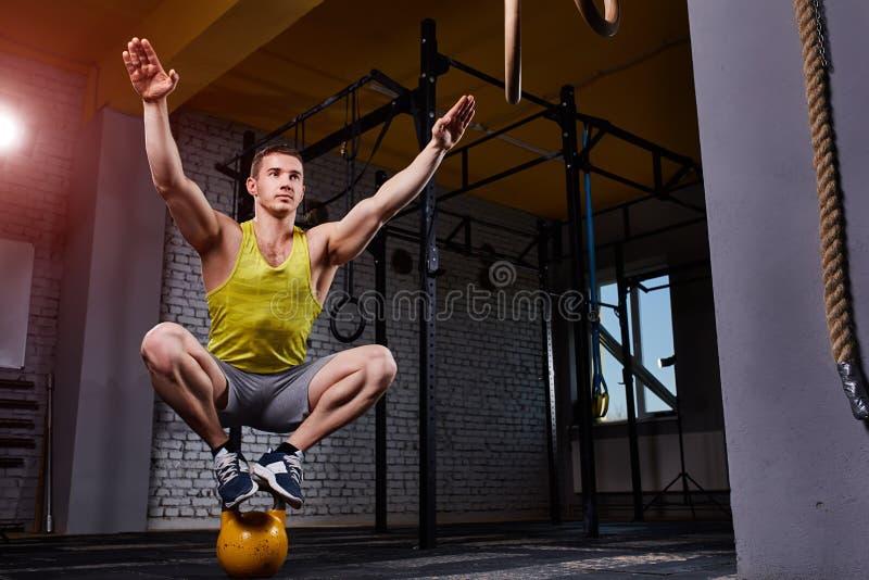 Position et équilibre convenables d'homme de forme physique de croix sur les kettlebells dans le gymnase contre le mur de briques photos stock