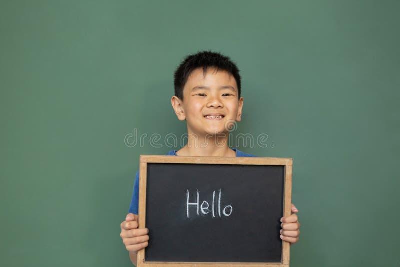 Position et tenir de sourire d'écolier bonjour une ardoise dans une salle de classe photographie stock