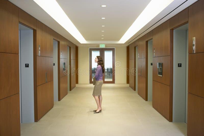 Position exécutive femelle dans la cage d'ascenseur photographie stock libre de droits