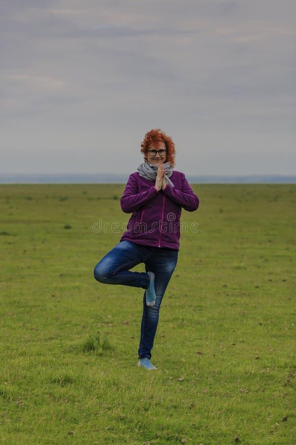 Position för träd för yoga för rödhårig mankvinna övande royaltyfri fotografi