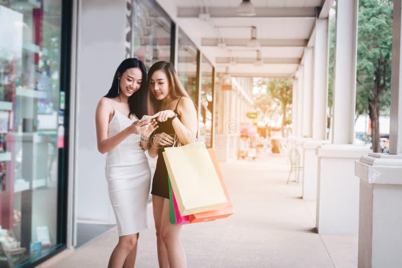 Position femelle asiatique de deux belle amis et apprécier des achats avec le sac de papier de participation images libres de droits