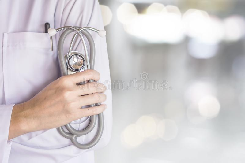 position femelle de docteur au-dessus de fond de tache floue de stéthoscope de participation de main d'hôpital photographie stock libre de droits