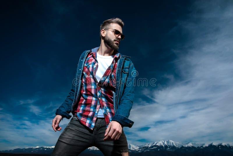 Position fraîche d'homme de mode contre le ciel bleu et les montagnes images libres de droits