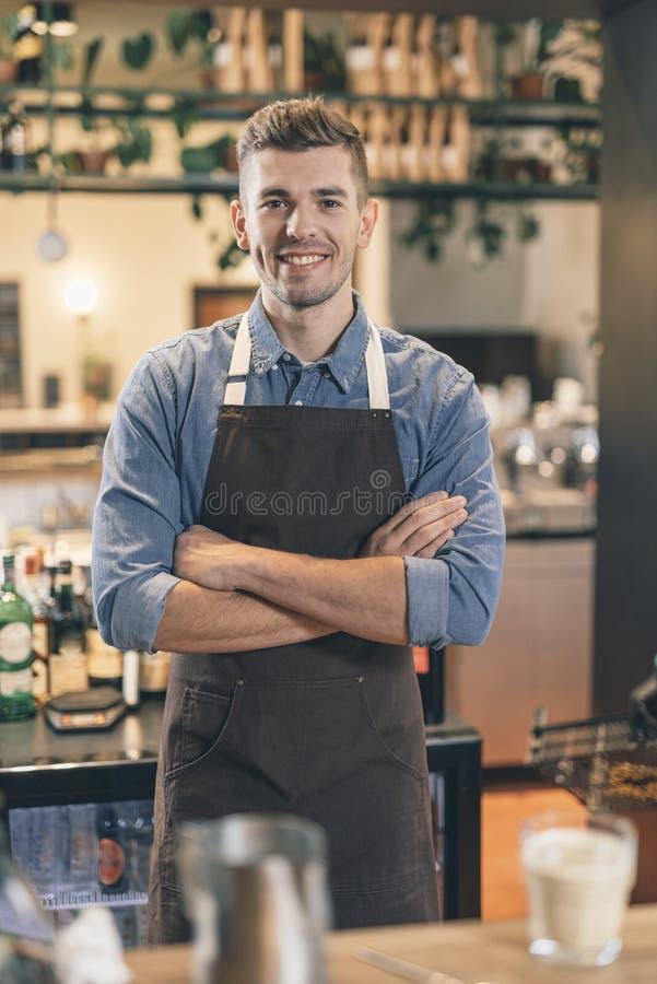 Position gaie de barman au compteur de barre avec les bras croisés images stock