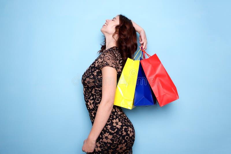 Position heureuse de jeune femme avec des sacs de cadeau sur le fond bleu image stock