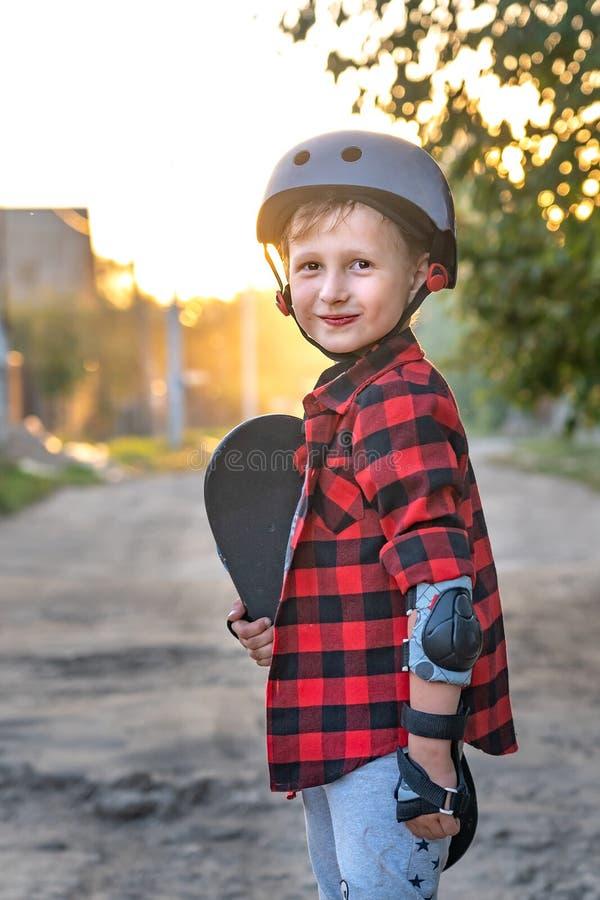 Position heureuse de petit garçon sur la route tenant un patin avec ses mains l'enfant s'est défendu, il a mis en main des gants  images stock