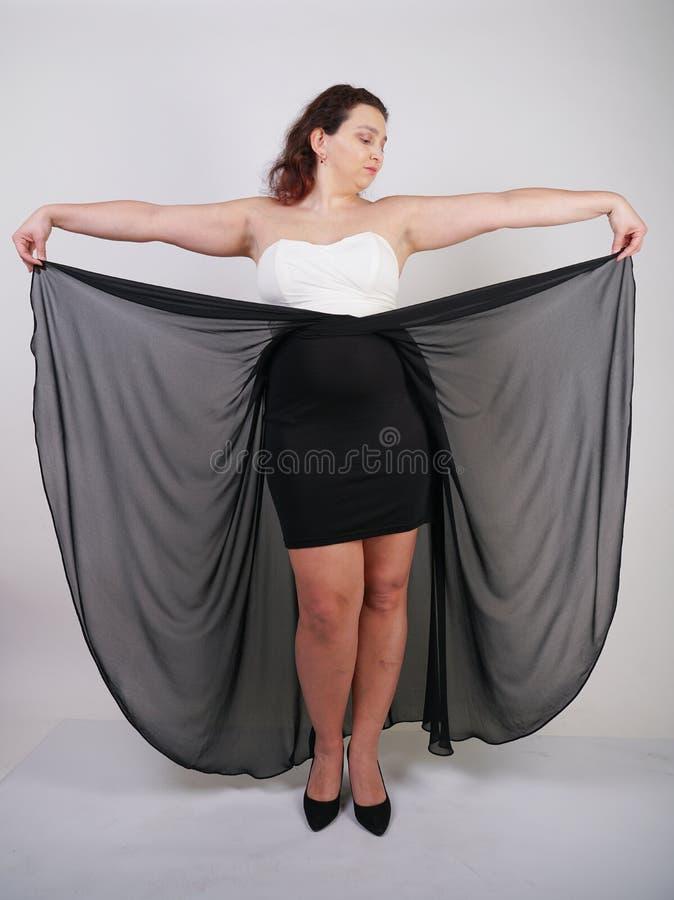 Position heureuse potelée avec du charme de femme dans la robe égalisante volante sur seul le fond blanc de studio photo libre de droits
