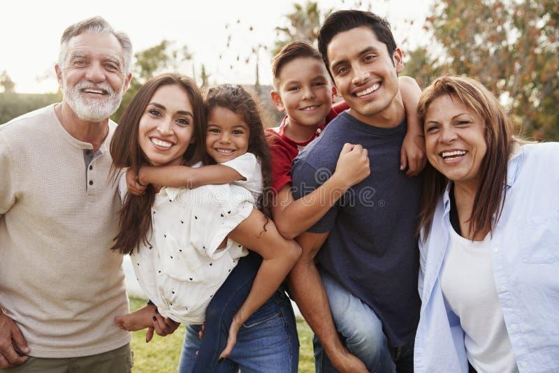 Position hispanique de famille de trois générations en parc, souriant à la caméra, foyer sélectif images libres de droits