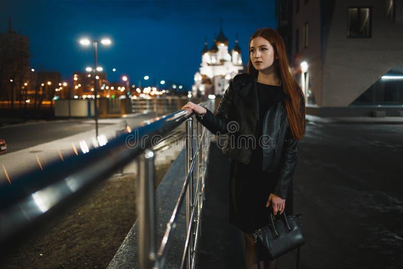 Position isolée de jeune femme dans la ville de nuit photos stock