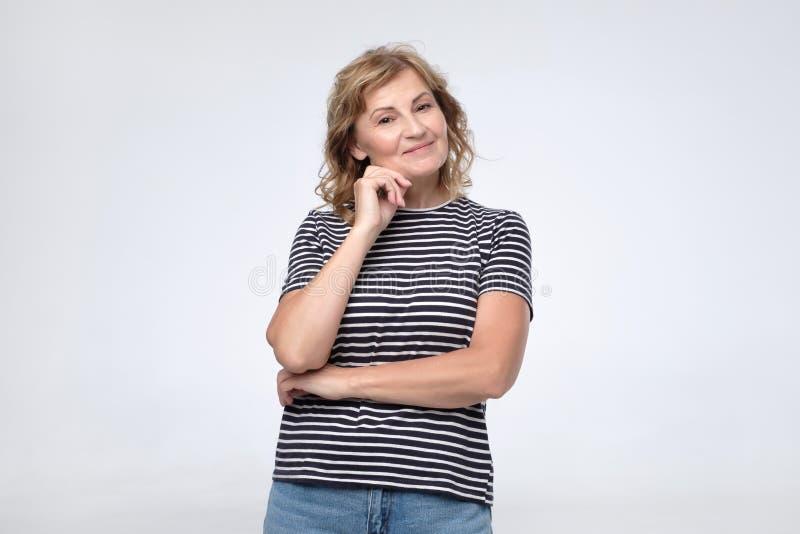 Position mûre heureuse de femme souriant à la caméra photos libres de droits