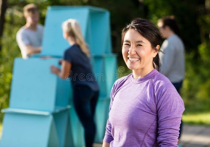 Position mûre heureuse de femme tandis qu'amis faisant la pyramide du plan photographie stock libre de droits