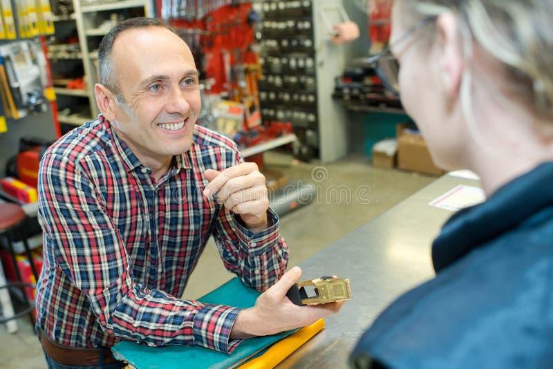Position masculine heureuse de client et de vendeuse dans le magasin image libre de droits