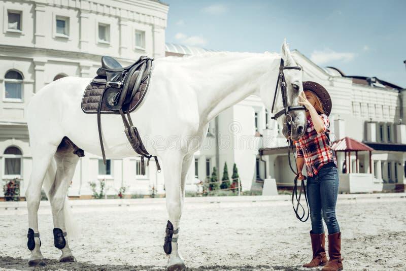 Position mignonne agr?able de fille pr?s de son cheval blanc image stock