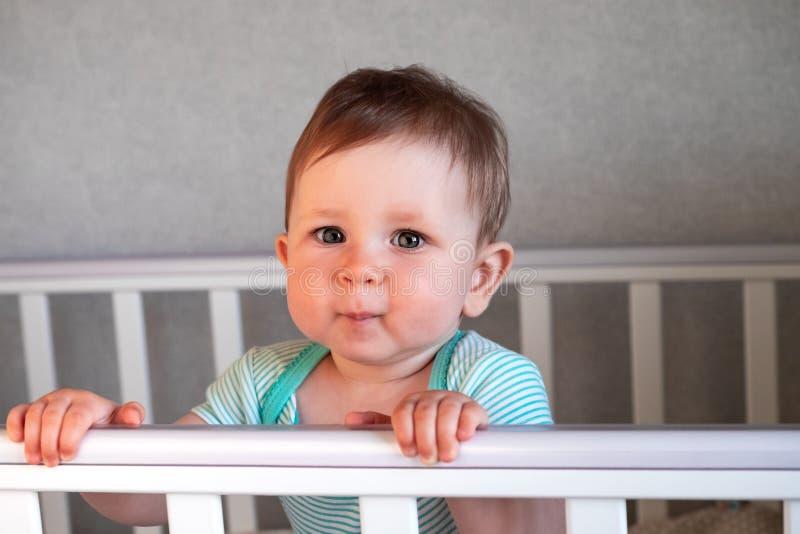 Position mignonne de bébé dans un lit en bois blanc photo stock