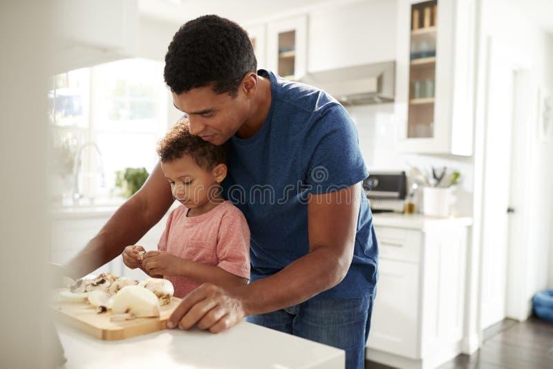 Position millénaire d'homme au plan de travail de cuisine préparant la nourriture avec son fils d'enfant en bas âge, fin, foyer s images libres de droits