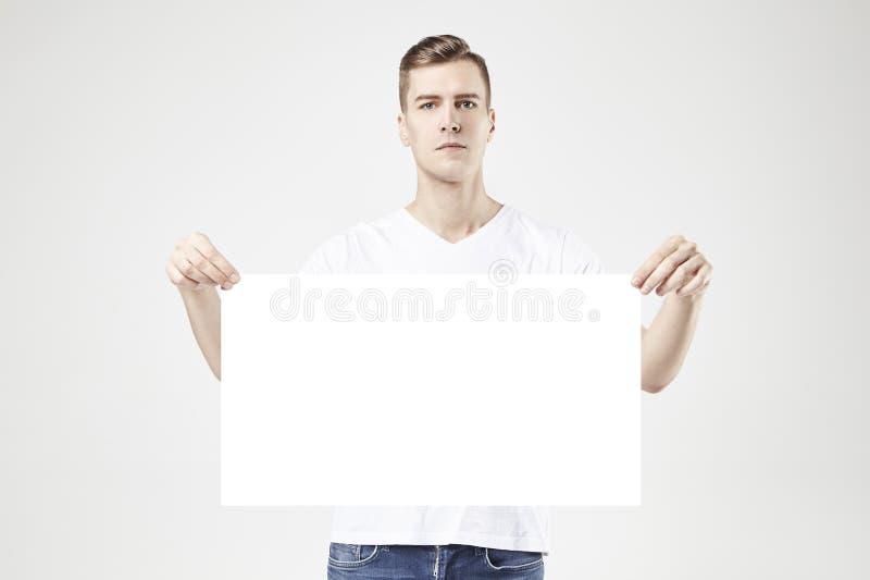 Position modèle d'homme bel avec la grande affiche ou feuille vide dans des mains, d'isolement sur le fond blanc, les jeans de po image stock