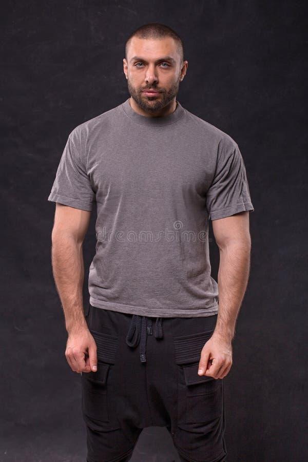 Position musculaire belle d'homme de barbe dans le studio au-dessus du fond foncé image libre de droits