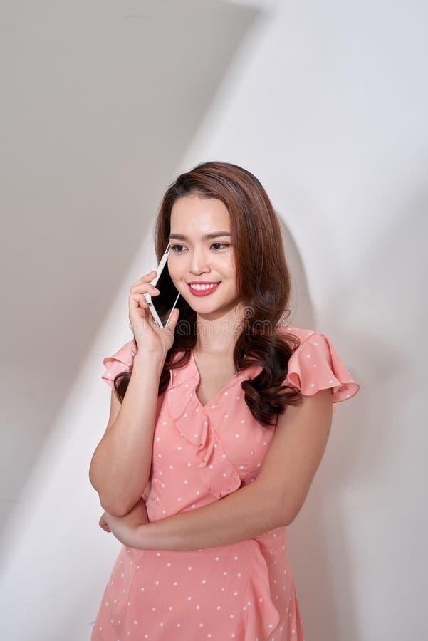 Position parlante de t?l?phone portable et de sourire de belle jeune femme asiatique sur le fond de ciment, t?l?phone appelant fe images libres de droits