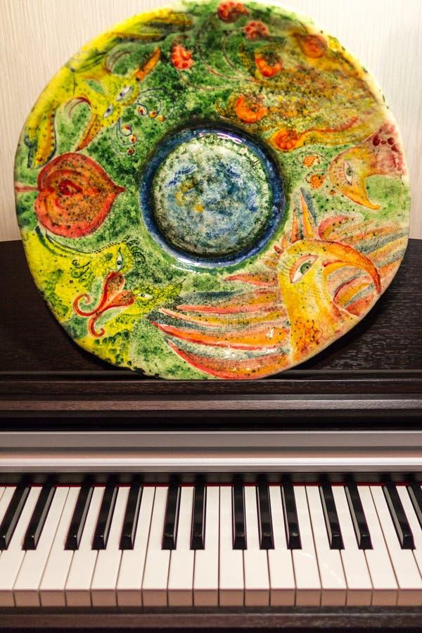 Position peinte faite main de plat d'argile sur le piano image libre de droits