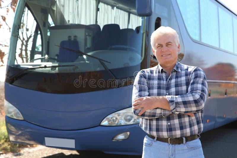 Position professionnelle de conducteur près d'autobus image stock