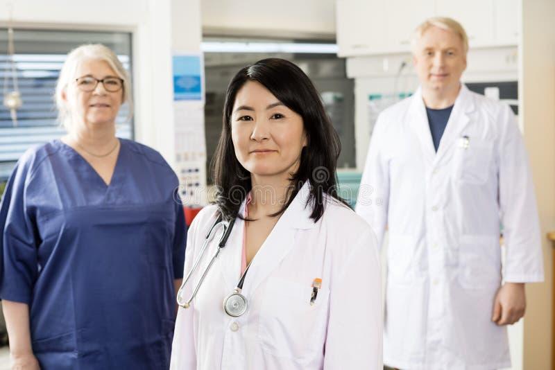 Position professionnelle médicale femelle avec l'équipe images libres de droits