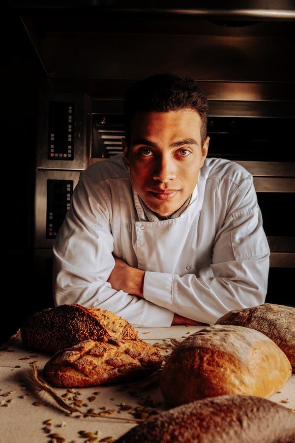 Position professionnelle sérieuse de boulanger près de table après fabrication du pain photo stock