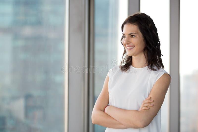 Position réussie de femme d'affaires dans le bureau regardant la fenêtre photo stock