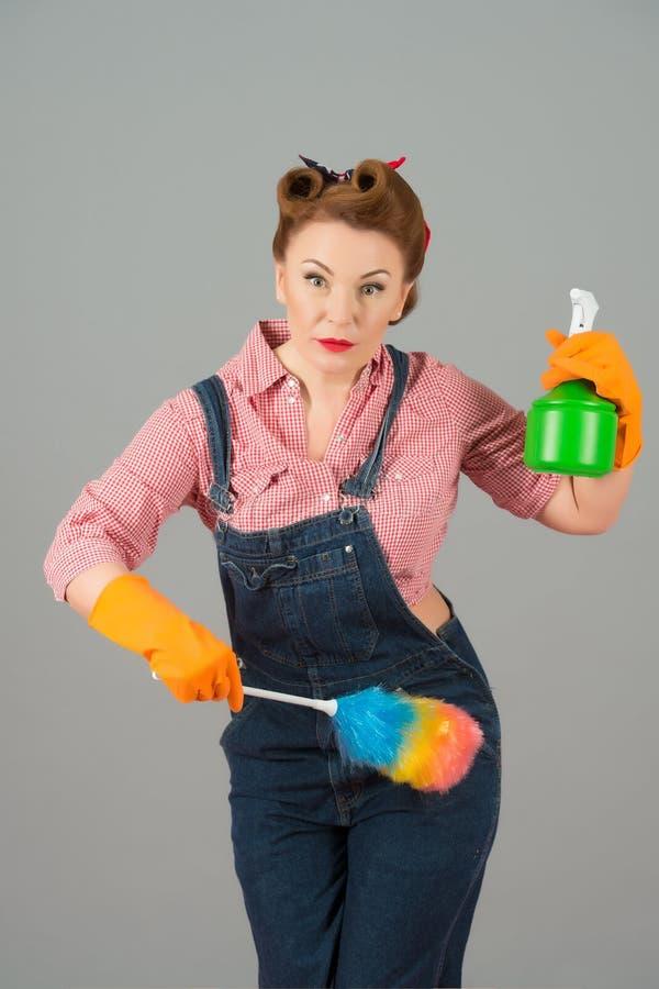 Position sérieuse de dame avec le pulvérisateur de brosse et d'eau de la poussière de plume images libres de droits