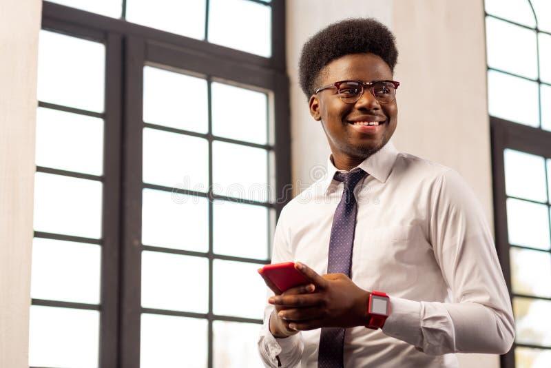 Position sûre positive d'homme avec son téléphone portable image stock