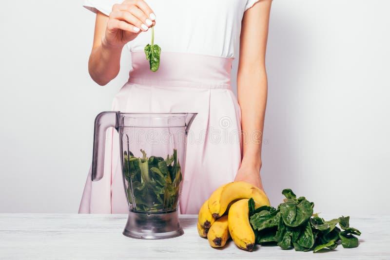 Position se tenante femelle de feuille près de table avec le mélangeur et les ingrédients pour la macédoine de fruits Dessus blan images libres de droits