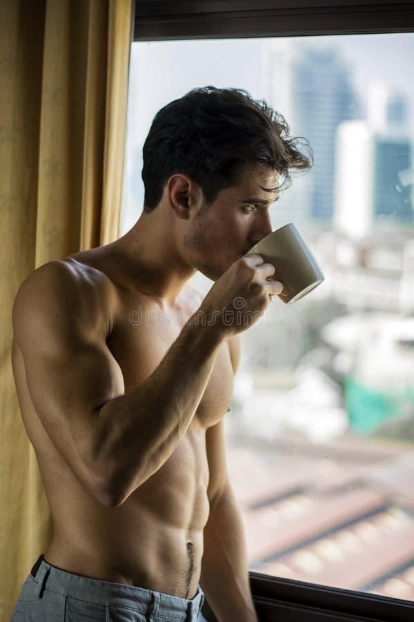 Position sexy de jeune homme sans chemise par des rideaux avec du café photos libres de droits