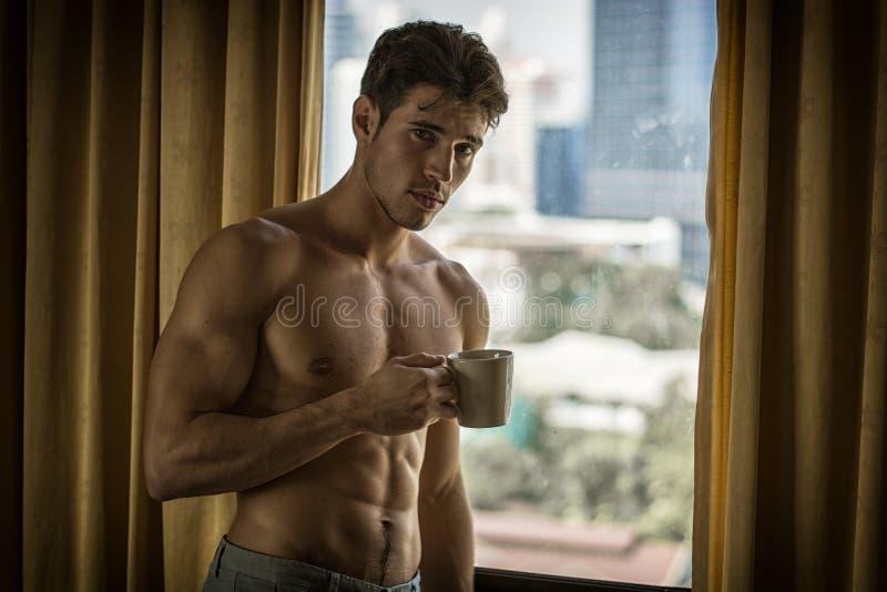 Position sexy de jeune homme sans chemise par des rideaux avec du caf? photo libre de droits