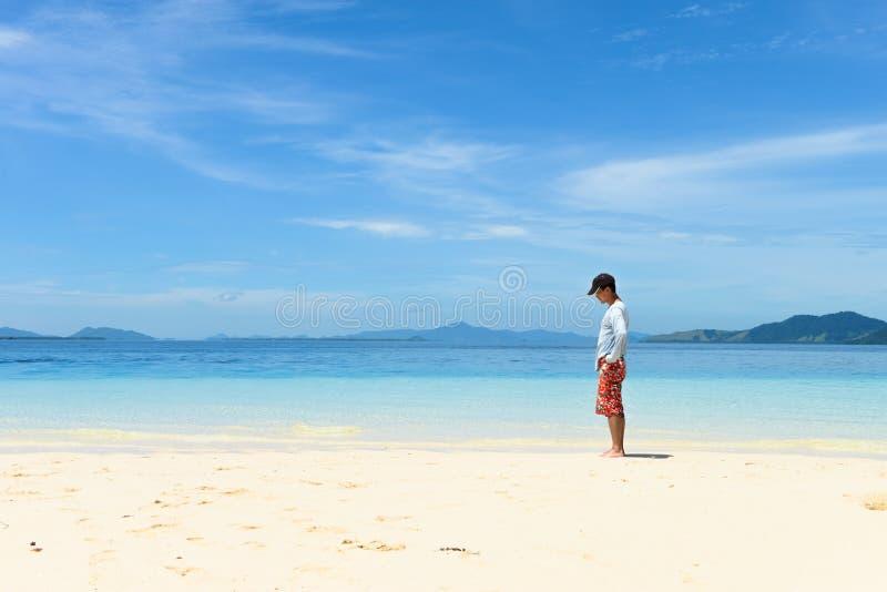 Position simple de jeune homme sur la plage blanche tropicale de sable photographie stock
