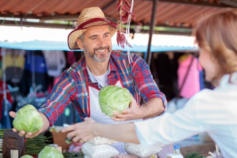 Position supérieure de sourire heureuse d'agriculteur derrière la stalle, vendant les légumes organiques dans un marché image libre de droits
