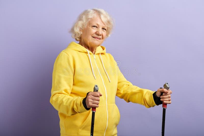 Position sup?rieure de femme avec les poteaux de marche nordiques dans le studio violet photos libres de droits