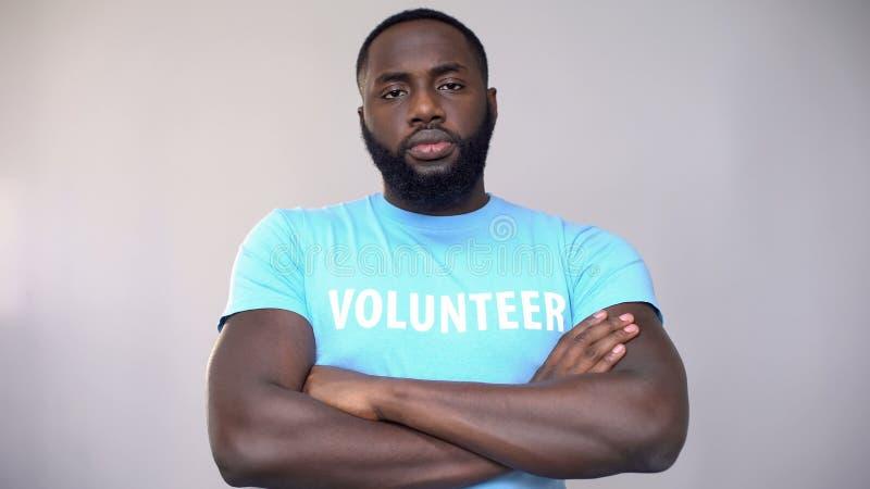 Position volontaire afro-américaine sérieuse avec des mains croisées, activité altruiste images libres de droits