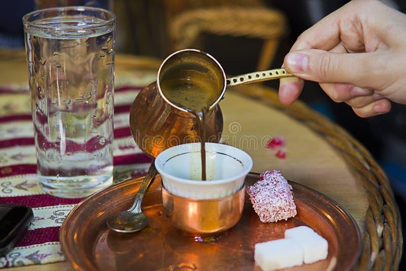 Positionnement bosnien de coffe complétant la cuvette de coffe image libre de droits