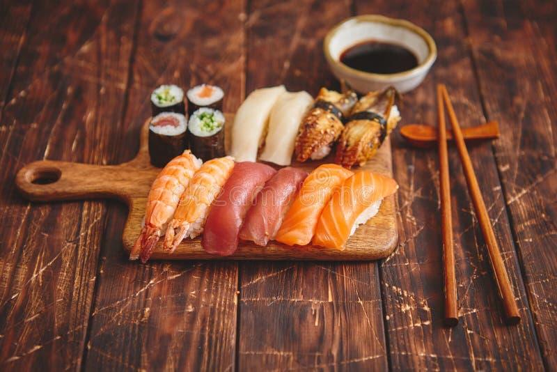 Positionnement de sushi Différents genres de petits pains de sushi sur le conseil servant en bois photographie stock libre de droits