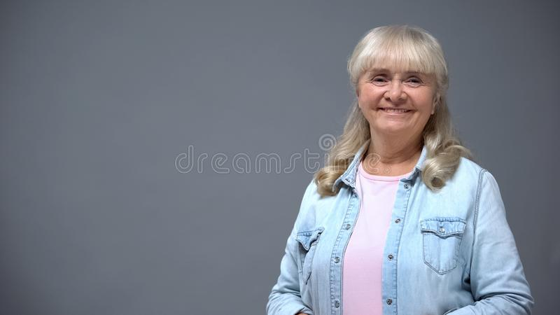 Positiv äldre dam i tillfällig kläder som isoleras på grå lycklig säker gamling royaltyfri foto