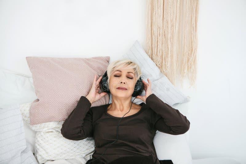 Positiv äldre kvinna som lyssnar till musik Den äldre utvecklingen och nya teknikerna arkivfoto